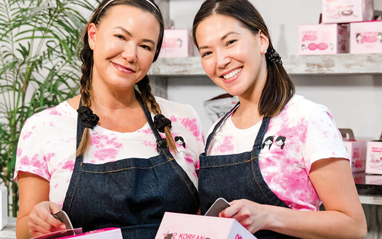 """Jennifer, left, and Michele Kaminski, with the to-go boxes for their 2 Korean Girls """"ghost kitchen."""" The sisters grew up spending time in their mother's Mishawaka, Indiana, restaurant. Years later, living in Miami and homesick for their mom and her Korean cooking, they started down the path that led to their food business."""